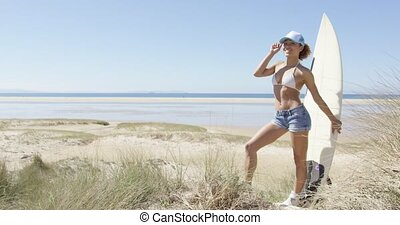 Female with surf admiring waterscape - Side view of young ...