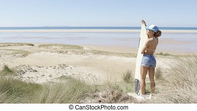 Female with surf admiring waterscape - Side view of young...