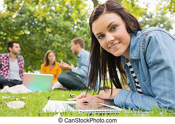 Female with tablet PC while others using laptop in park -...