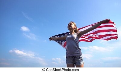Female with USA flag in nature - Side view of young female...