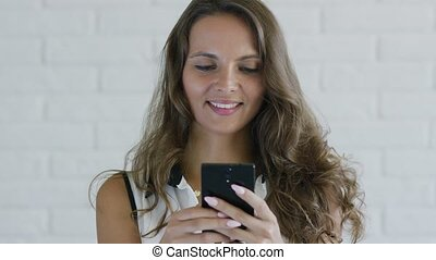 Female with wavy hair browsing smartphone