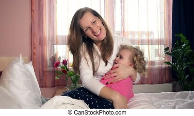 Female woman calm down little worried child girl by embracing and swinging