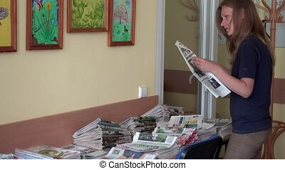 Female woman reading newspapers at library