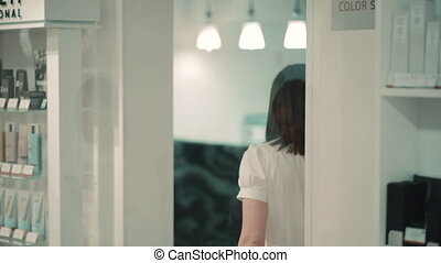 Female worker and client talking and walking during working day in spa salon. Two young women communicate and walk in bright room with shelves of cosmetic products. Closeup view of beautiful ladies have conversation before wellness procedure. They wearing casual clothes. Concept: people, healthcare...