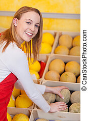 Female Worker Arranging Honeydew In Box At Grocery Store