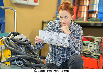female worker checking clipboard in warehouse