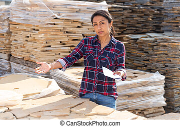 Female worker checking quantity of natural stone tiles