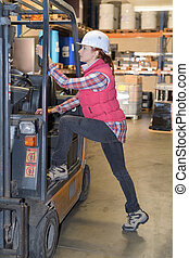 female worker climbing into cab of forklift truck