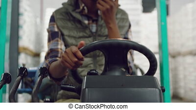 Female worker driving forklift in a warehouse - Front view ...