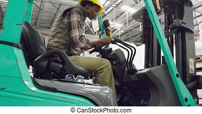 Female worker driving forklift in a warehouse