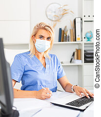 Female worker enters patient data into laptop