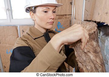 Female worker fitting insulation