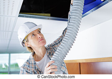 female worker fitting ventilation system in buildings...