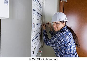 female worker fixing a fuseboard