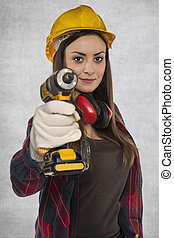 Female worker holding an electric screwdriver