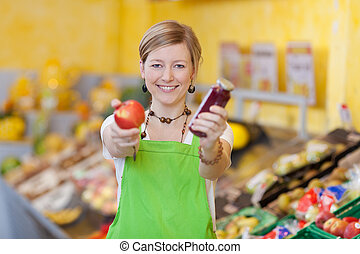 Female Worker Holding Apple And Jam Jar In Grocery Store