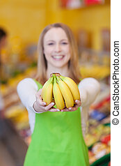 Female Worker Holding Bananas In Grocery Store