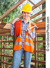 Female Worker Holding Pipe And Hammer At Site