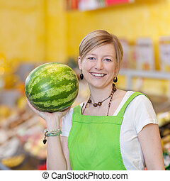 Female Worker Holding Watermelon In Grocery Store