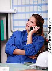 Female worker in blue overalls on the office phone