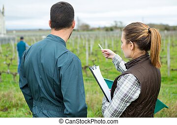 female worker in vineyards pointing at something