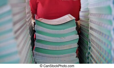 Female worker lays out a large stacks of paper from the box in the typography