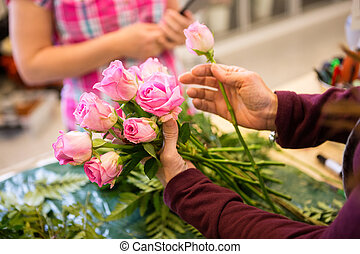Female Worker Making Bouquet Of Roses For Customer