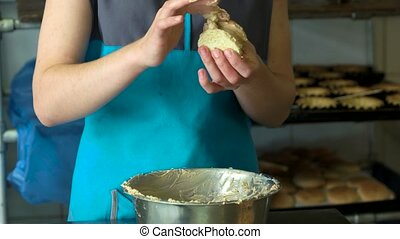 Female worker making cookie at bakery. Woman cooking biscuit...