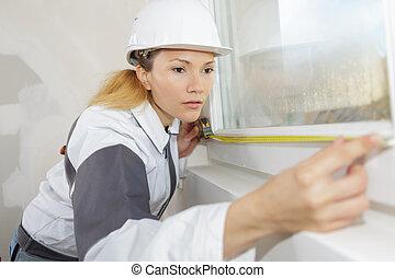 female worker measure the window