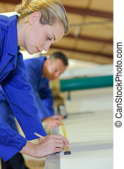Female worker measuring and marking material