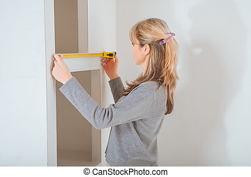 female worker measuring with tape measure