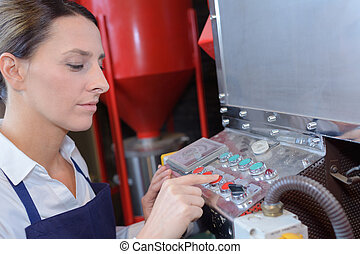 female worker operating a machine in a factory