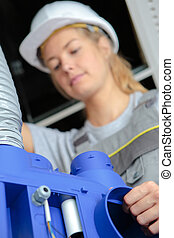 female worker operating machine in factory
