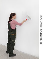 Female worker painting wall in a room