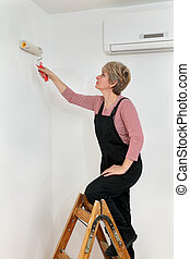 Female worker painting wall in a room, home renovation