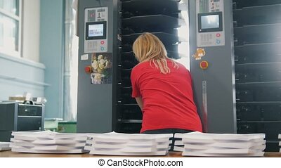 Female worker puts paper in the printing machine