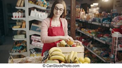 Female worker restocking fresh products into boxes at store...