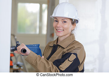 female worker sanding the wall