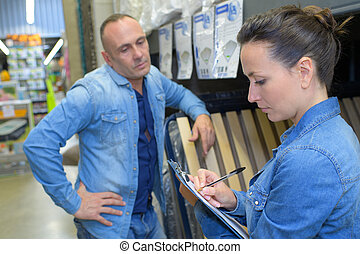 female worker showing wood section to customer in hardware store