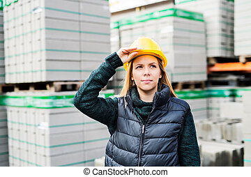 Female worker standing outside a warehouse.