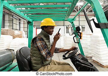 Female worker talking on walkie-talkie while driving forklift in warehouse