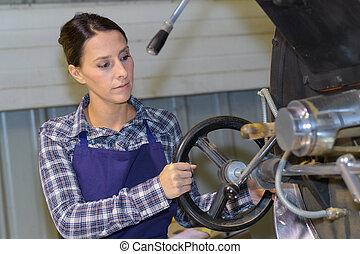 Female worker turning wheel on machine