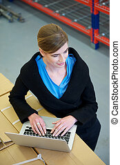 Female worker typing on laptop computer in warehouse