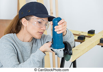Female worker using angle grinder