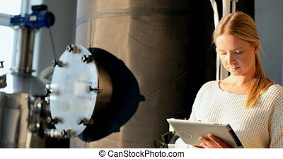 Female worker using digital tablet in distillery factory. Storage tanks in the background 4k