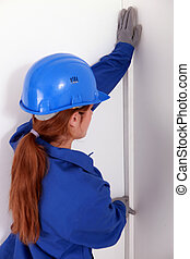 female worker wearing a blue jumpsuit is checking the wall's straightness