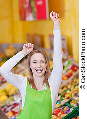 Female Worker With Arms Raised In Grocery Store