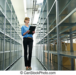 Female worker with clipboard, oraganizing inventory and stock in warehouse