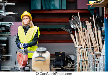 Female worker with jackhammer in a warehouse.