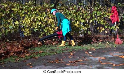 Female worker with leaf blower blowing leaves in parking lot. Gimbal motion shot.